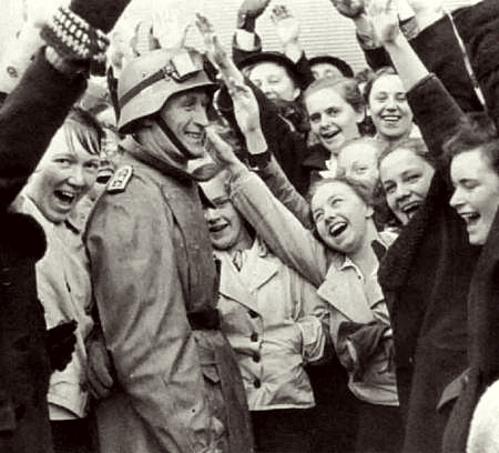 Young Austrian girls greet a German soldier with an enthusiastic sieg heil